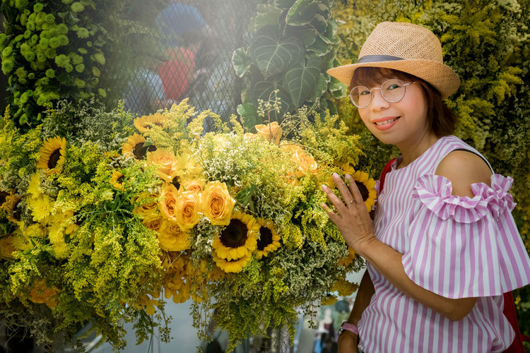 lady posting in the garden Plant Smiling Happiness Women Hat One Person Adult Nature Emotion Looking At Camera Leisure Activity Growth Standing Glasses Young Women Young Adult Real People Females Day Gardening Sun Hat Outdoors