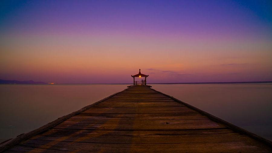 Gazebo on pier over sea against orange sky