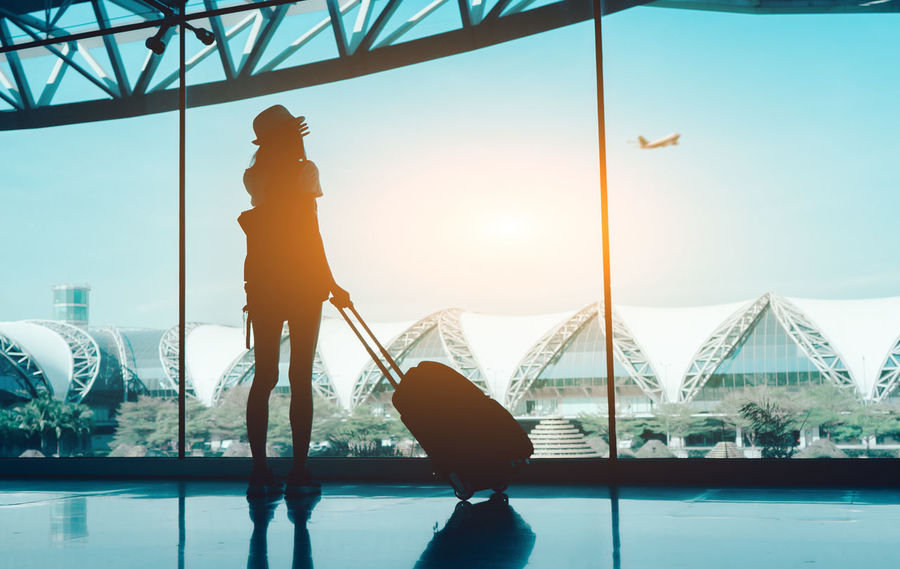 Silhouette woman travel with luggage looking without window at airport terminal international or girl teenager traveling in vacation summer relaxation holding suitcase and backpack Transport Boarding Gate Plane Reflection Silhouette Standing Tourist Travel Waiting Woman Airplane Airport Bag Baggage Claim Flight Girls Hall Lifestyles Luggage People Suitcases Of Memories Terminal Tourism Window