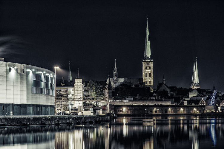 Steeples Architecture Building Exterior Built Structure City City Life Illuminated Low Angle View Marienkirche Lübeck Night No People Outdoors Place Of Worship Reflection River Sky Spire  St. Jakobi Kirche Zu Lübeck Steeple Tall - High Tourism Tranquil Scene Untertrave Water Waterfront