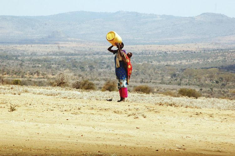 A woman with a child on her back drinks the last drop of water from a jerrycan at Samburu west county, Kenya. Water is Usually scarce in many dry areas of the country. Water Mother Motherhood Mother And Child Mother's Day Motherslove Mothers Waterdrops Drought Drought Period Droughtisreal Drought Global Warming Drought.