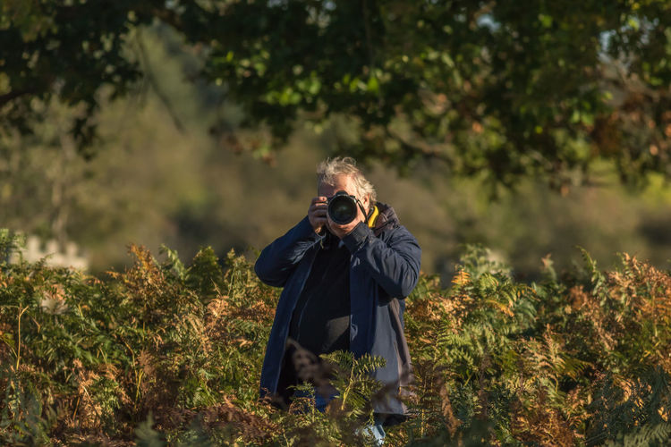 Senior Man Photographing Against Trees