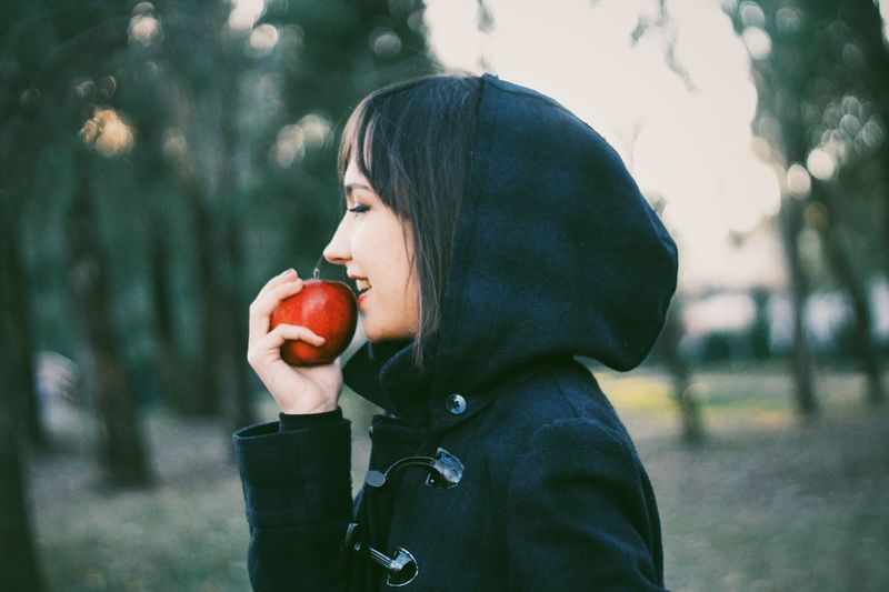Smiling Young Woman Holding Red Apple While Standing At Park