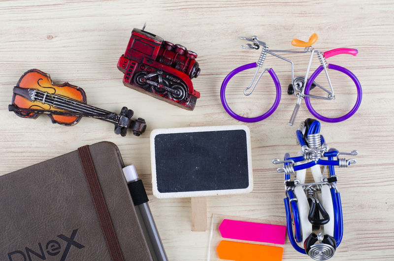 top view vacation and holiday concept word TRAVEL with accessories on wooden background Table Still Life High Angle View Indoors  No People Pen Wood - Material Music Key Directly Above Musical Instrument Group Of Objects Glasses Large Group Of Objects Scissors Publication Close-up Screwdriver Book Personal Accessory