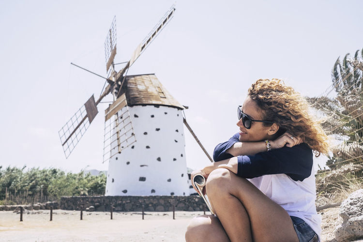 Woman Sitting Against Traditional Windmill In City