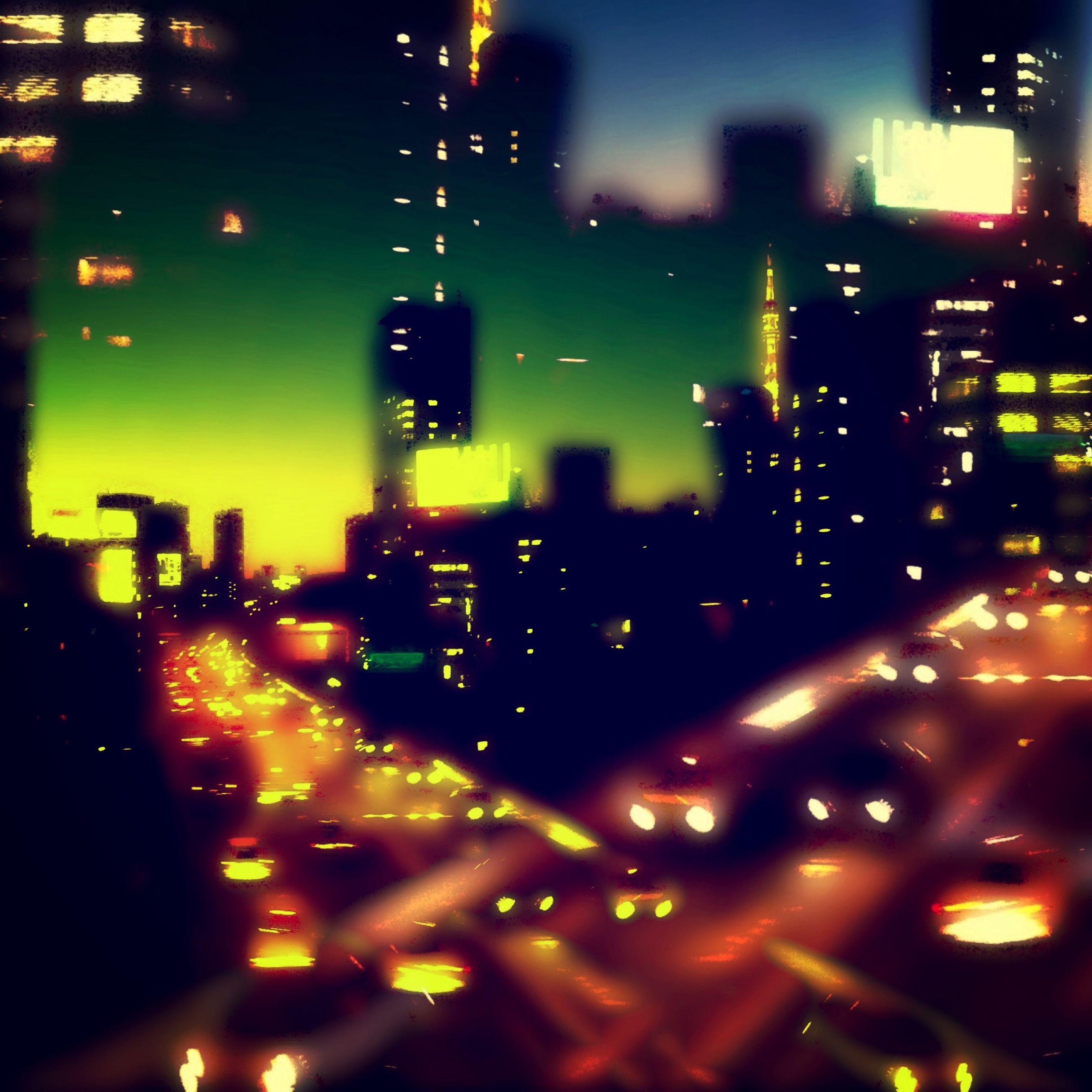 illuminated, night, city, building exterior, architecture, built structure, cityscape, skyscraper, street, city life, city street, road, office building, wet, window, light - natural phenomenon, transportation, no people, glass - material, defocused
