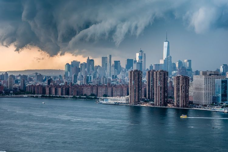 East river by modern buildings against cloudy sky at manhattan