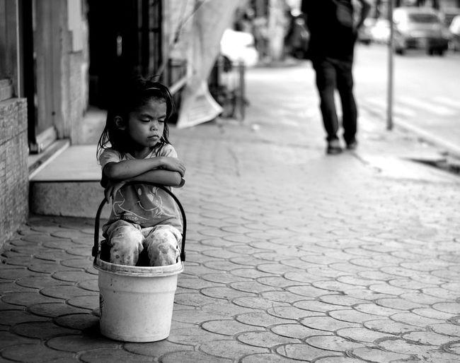 Girl relaxing in bucket on sidewalk