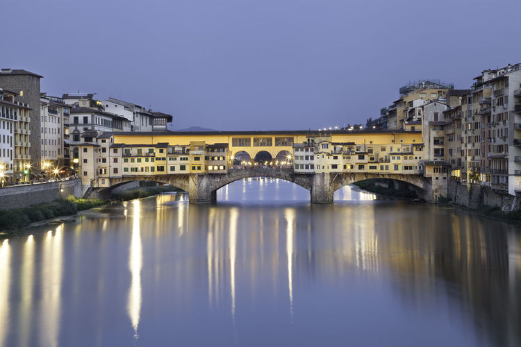 Illuminated Ponte Vecchio Over Arno River In City At Dusk