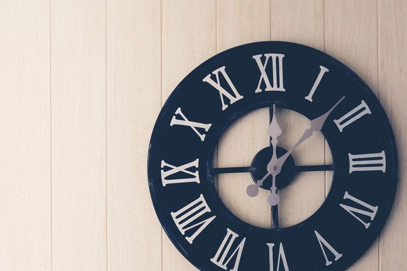 Close-up of clock on wooden wall