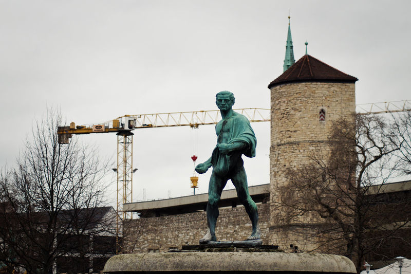 Low angle view of statue and old building against crane and sky