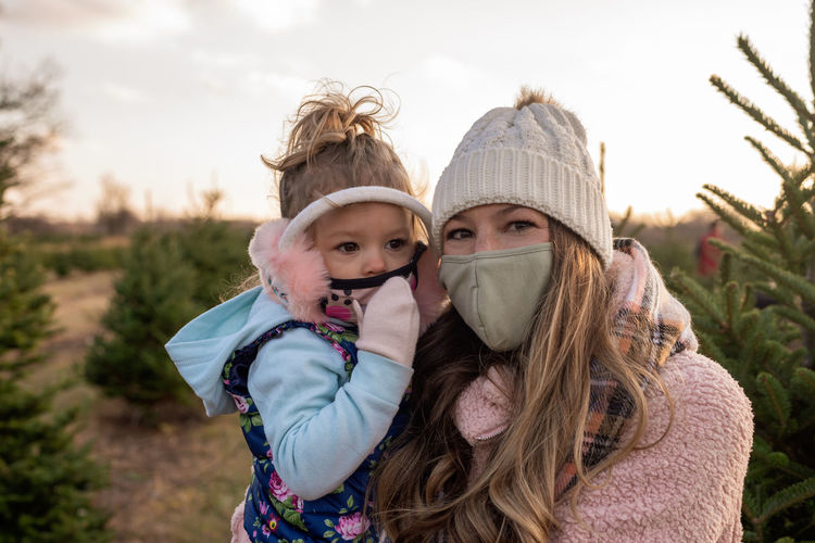 Portrait of mother with daughter wearing mask standing at field