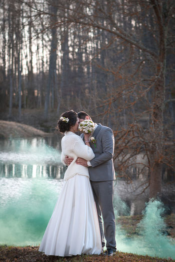 Newlywed Couple Kissing While Standing Against Lake