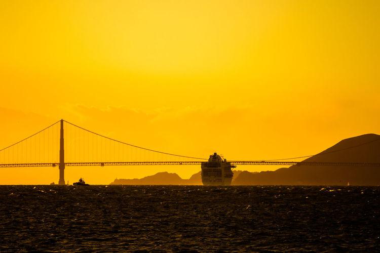Silhouette of suspension bridge against sky during sunset