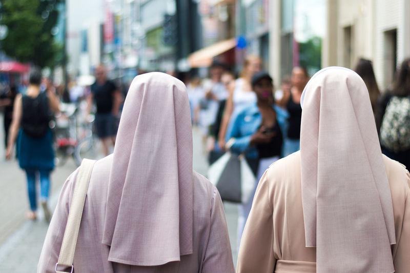 Rear view of nuns walking on street in city