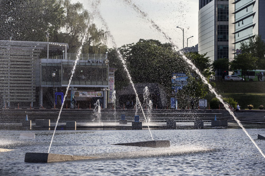 Architecture Building Built Structure City City Life City Street Day Enjoyment Fountain Fun Hangang Park Leisure Activity Lifestyles Motion Outdoors Park Spraying Tree Water Drops