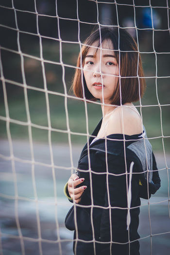 Portrait of beautiful young woman standing at goalpost