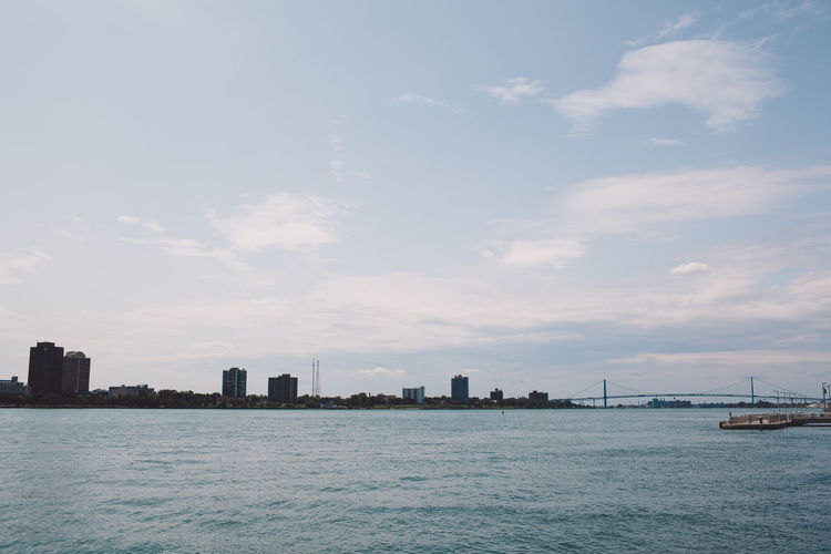 Sea By Cityscape Against Sky