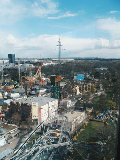 High Angle View Of Amusement Park In City Against Cloudy Sky
