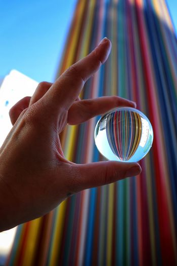 Low angle view of hand holding crystal ball