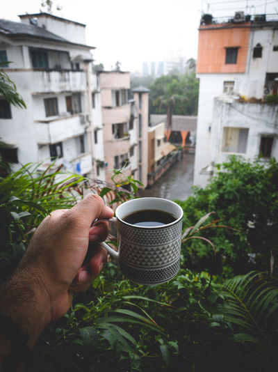 Cropped image of hand holding coffee cup against building