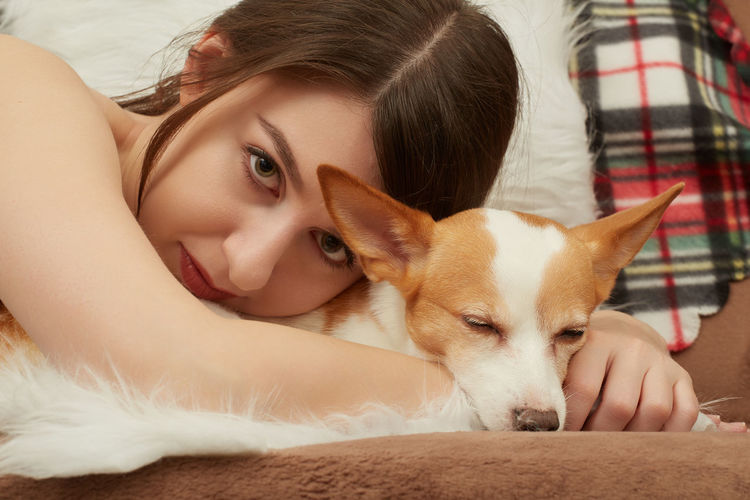 Portrait of young woman lying down with dog at home