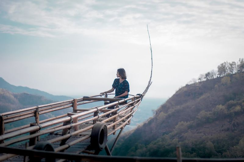 Woman sitting on wood at observation point against mountain and sky