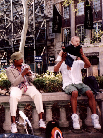 Adult Adults Only Black Men Building Exterior Carrying Baby Casual Clothing City Day Full Length Men Mid Adult Mixed Race Only Men Outdoors People Playing Portrait Senior Adult Senior Men Sitting Street Performer Togetherness Trumpet Two People White Baby