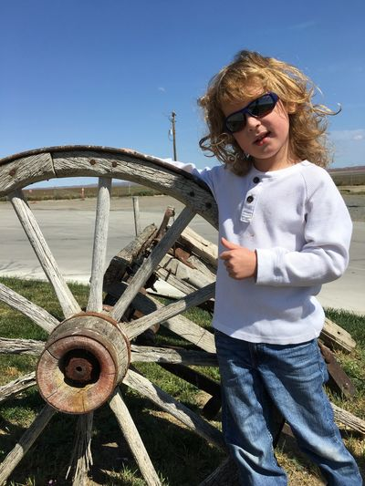 Portrait of boy wearing sunglasses while standing with wheel at roadside