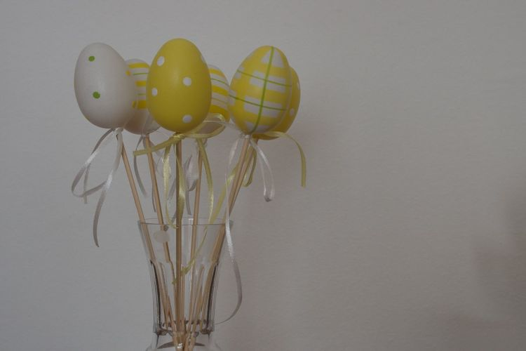 Studio Shot Indoors  White Background No People Close-up Still Life Copy Space Vulnerability  Fragility Creativity Egg Easter Yellow Vase Ribbon Decoration Easter Decoration Bow