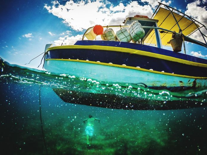 Low angle view of man swimming under boat in the water