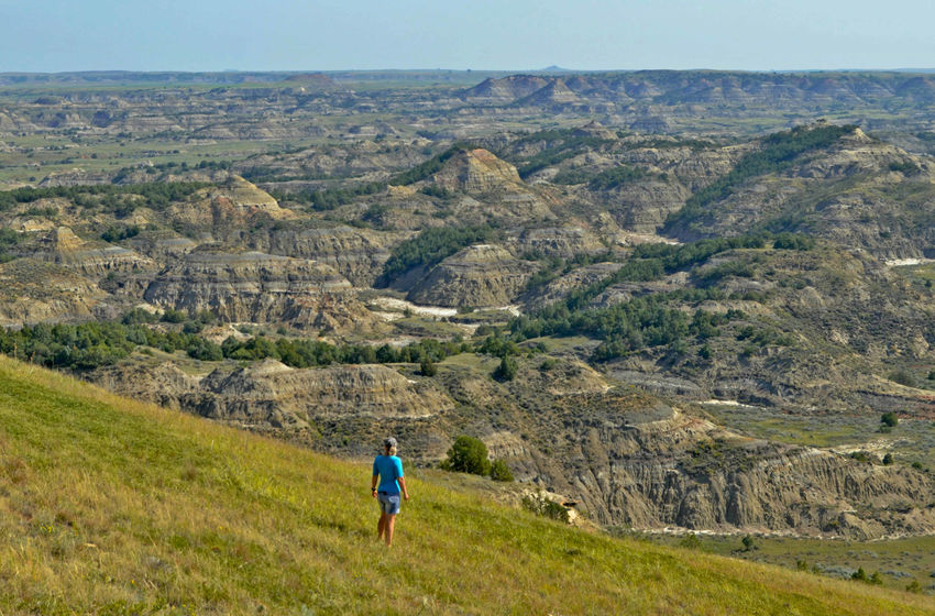 Badlands Freedom Hiking In The Hills Nature North America North Dakota Vista Blue Shirt Gazing Person Gazing Wom Landscape With People In Outdoor Women Outdoors Roadtrip Rugged Landscape Sloping Hills Sweeping View Travel Destinations Wild Landscape Woman And Landscape Woman In Nature
