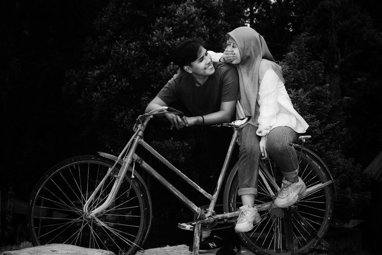 Couple sitting on old bicycle