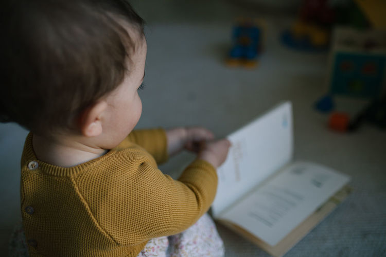 Side view of cute baby girl playing with book at home