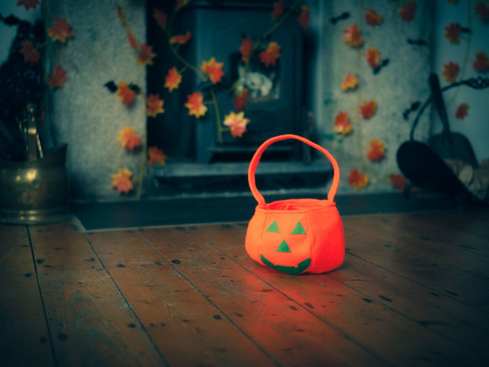 Close-up of pumpkin bag on wooden floor at home