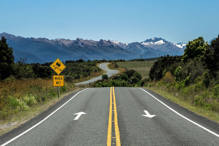 Road sign and zigzag road in new zealand against clear blue sky