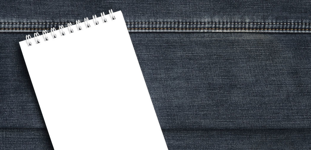 Directly above shot of empty spiral notebook on denim