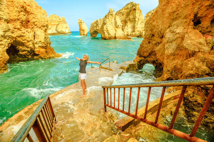 The end of staircase that leads Ponta da Piedade. Pier for small boats for sightseeing between arches and natural caves. Freedom lifestyle tourist enjoying in Lagos, Algarve, Portugal. Windy and waves Lagos Portugal Algarve Portugal Algarve Coastline Algarve Beach Algarve Cliffs And Beach Beach Sea Town Seascape Boat Portrait Pier Aerial View Cliff Jetty Boats Woman Females Girl Selfie Model Ponta Da Piedade Ponta Da Piedade Lagos Lighthouse Bay Water Rock Rock - Object Beauty In Nature Nature Leisure Activity Rock Formation One Person Railing Lifestyles Real People Day Solid Full Length Standing Scenics - Nature Sunlight Outdoors