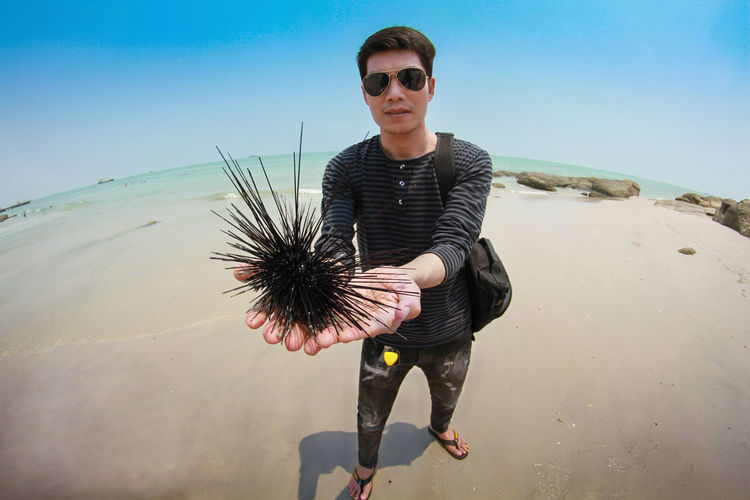 Portrait of young man holding urchin at beach against sky