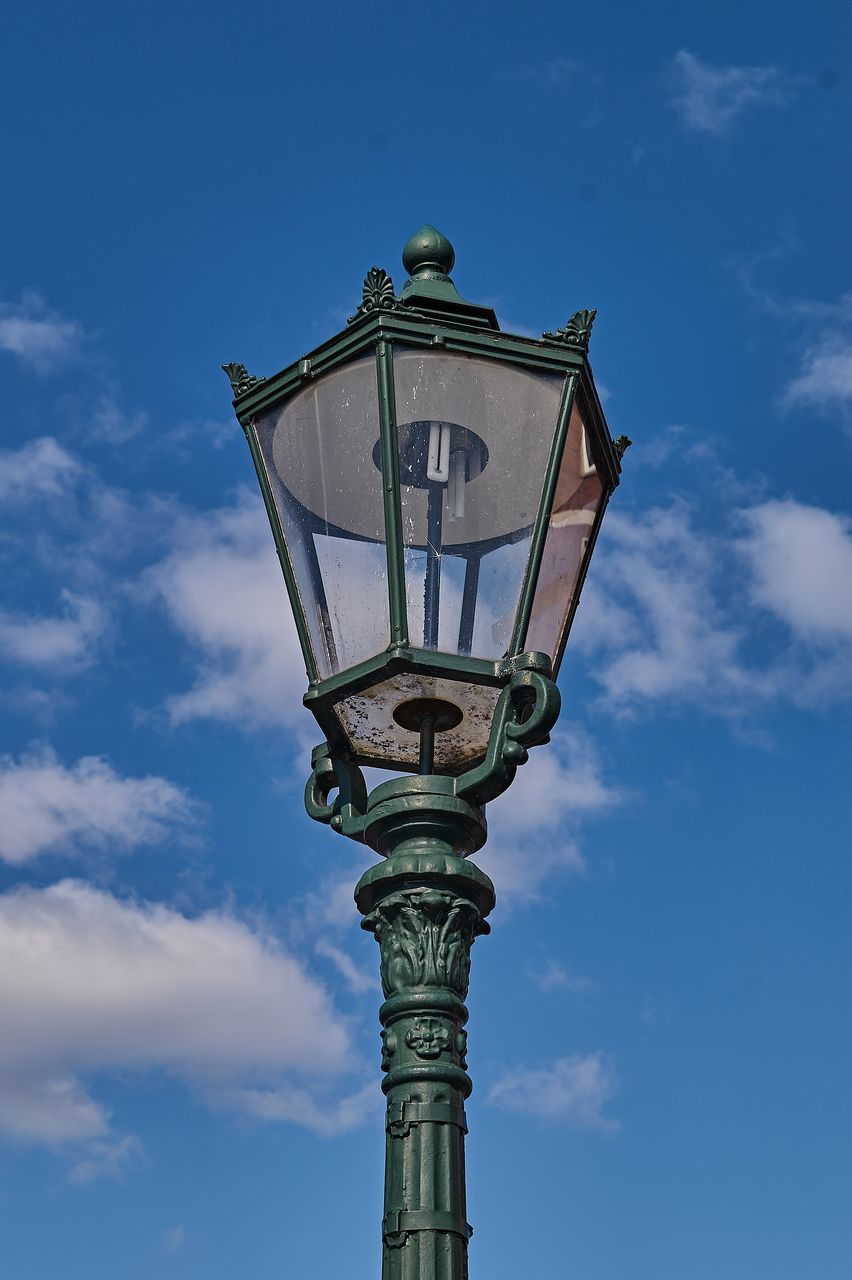 low angle view, sky, lighting equipment, cloud - sky, street, street light, architecture, built structure, no people, nature, blue, day, outdoors, building, gas light, tall - high, building exterior, pole, clock, tourism