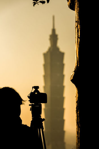 Silhouette of camera against sky during sunset