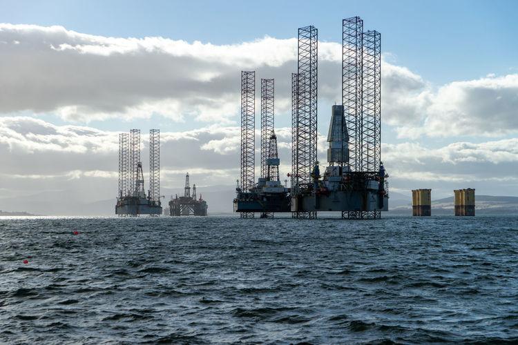 Cranes in sea against sky