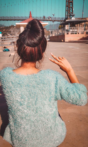 Rear view of woman gesturing peace sign while sitting in city