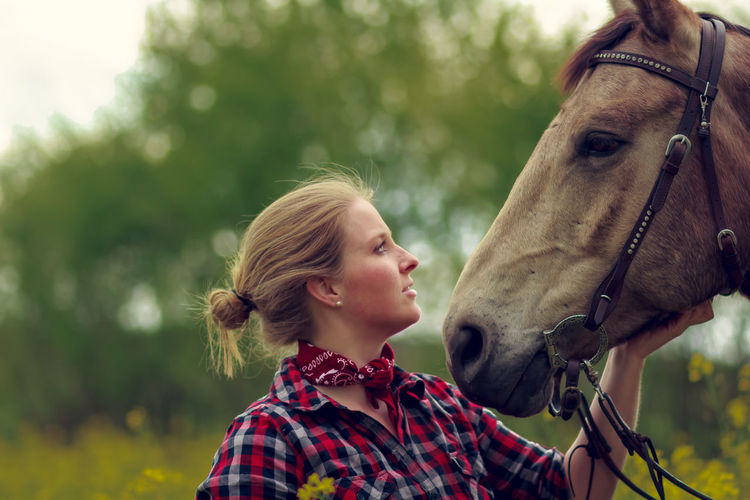 One Animal Animal Child Agriculture Checked Pattern Rural Scene People One Person Girls Children Only Day One Girl Only Care Nature Domestic Animals Blond Hair Grass Outdoors Bonding Animal Themes Pet Portraits
