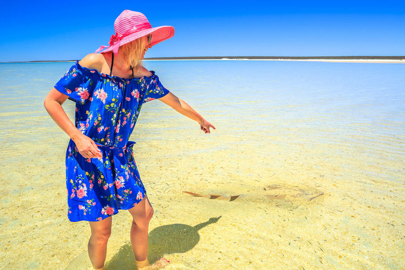 A tourist woman pointing at Guitarfish or Rhynchobatus Australiae at Shell Beach in Shark Bay Area. Shell Beach is famous for shells and clear waters. Coral coast in Western australia. Australia Australian Sea Beach Seascape Western Australia Clear Water Water Stingray Sting Ray  Sea Eagle Shell Beach Shell Beach Australia Guitarfish Denham Woman Girl Horizon One Person Real People Leisure Activity Land Lifestyles Women Nature Standing Sunlight Beauty In Nature Sky Clothing Horizon Over Water Casual Clothing Fashion Hairstyle