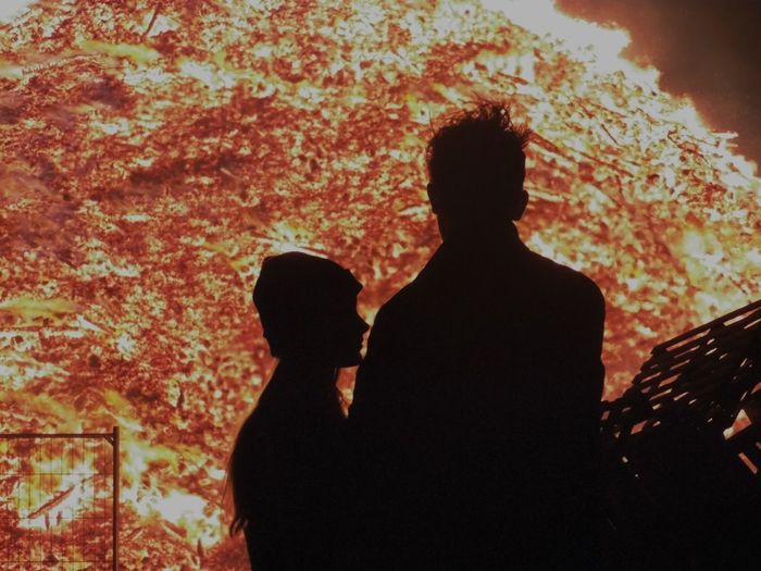 Silhouette Of Man And Woman Standing Against Fire At Night