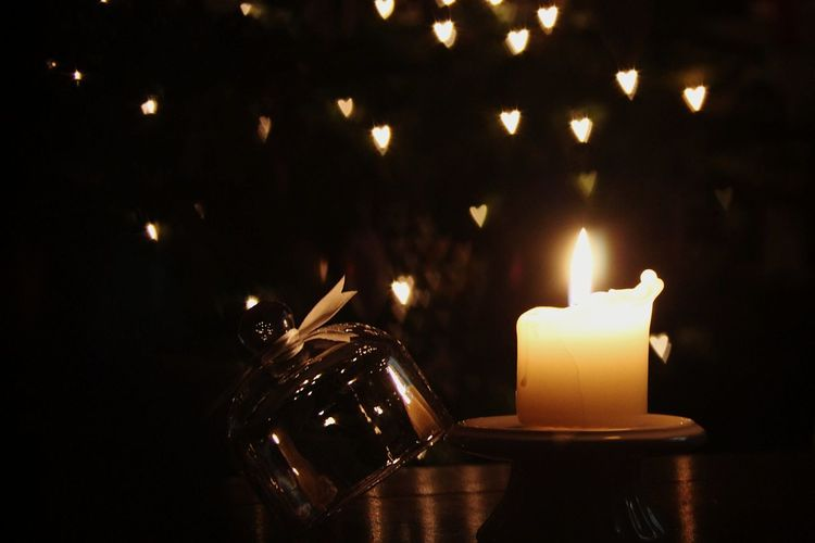 Close-up of burning candle on table at night