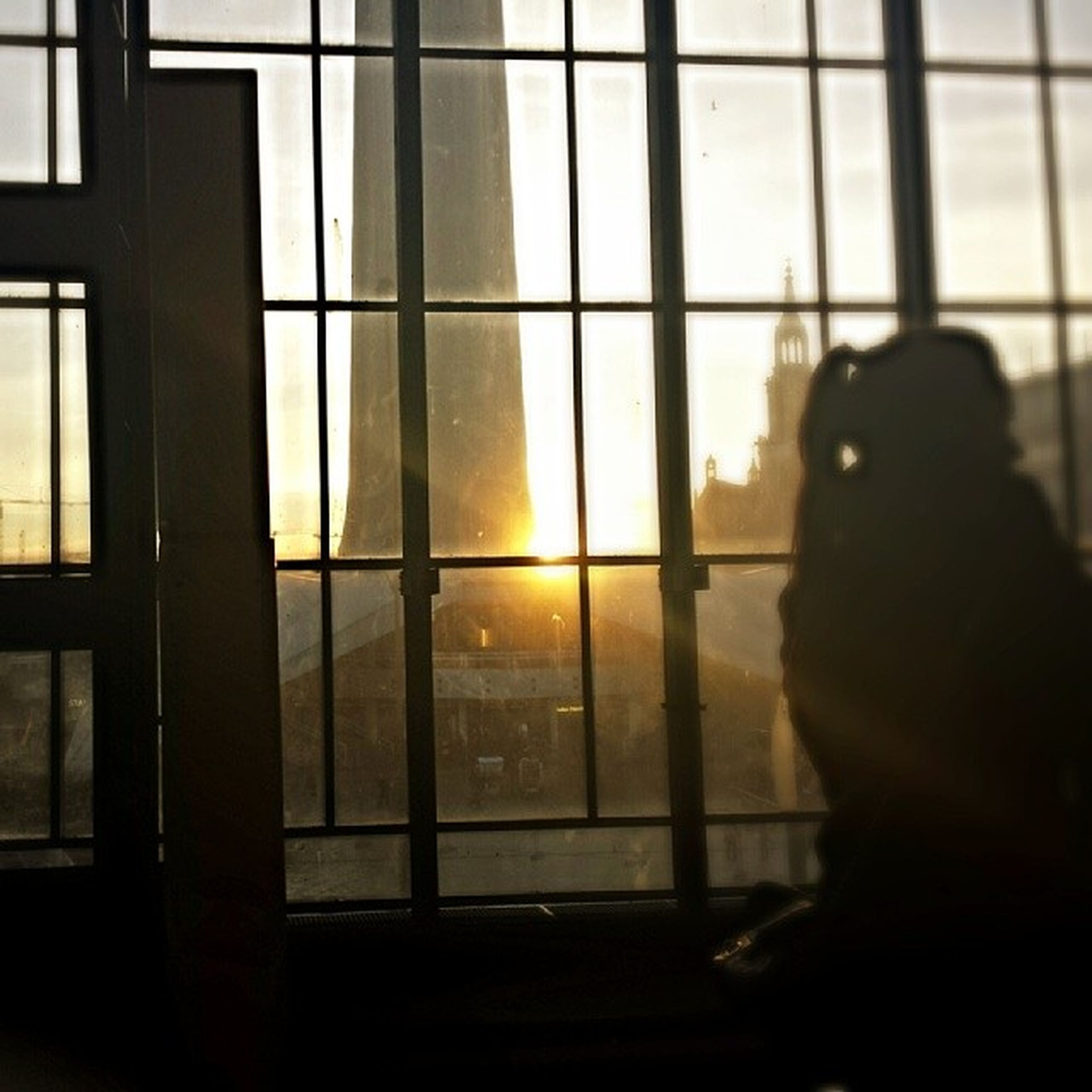 window, indoors, glass - material, silhouette, transparent, built structure, architecture, sunset, sunlight, glass, curtain, looking through window, reflection, building exterior, modern, building, sky, home interior