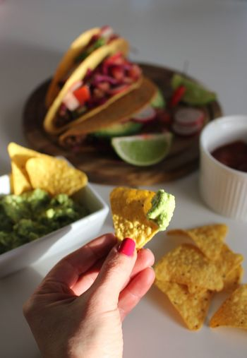 Cropped hand of woman holding tortilla chip by table