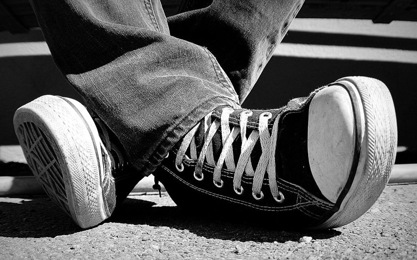 Low section of man wearing canvas shoes on footpath